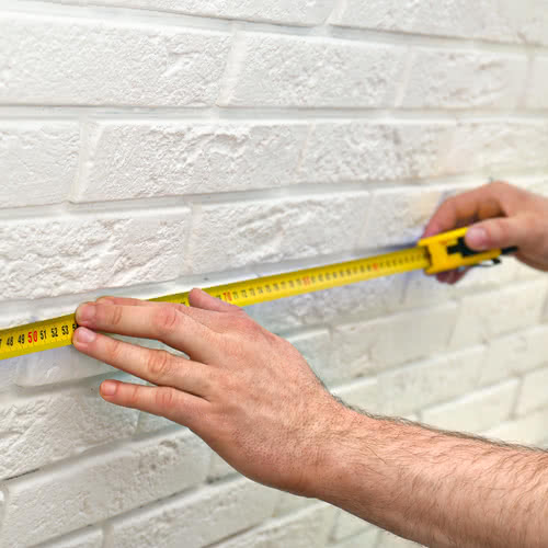 man measuring a white brick wall with a tape measure