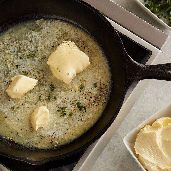 Butter melting in a cast iron skillet with herbs