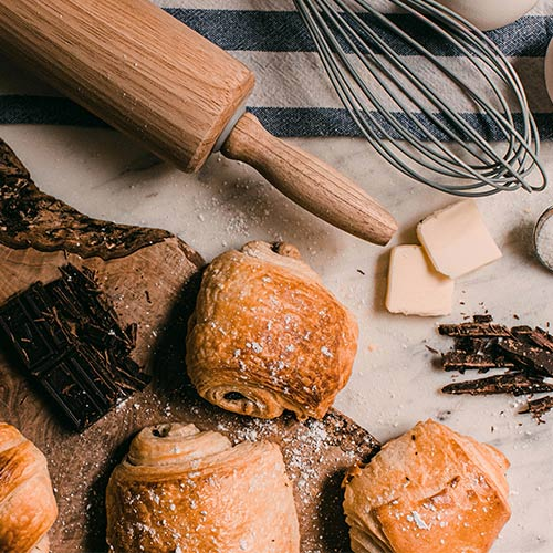 Chocolate croissants next to butter, a wooden rolling pin, and a whisk