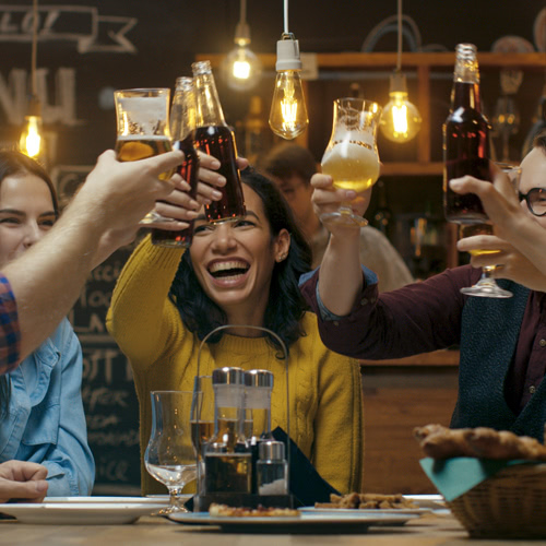 A group of smiling friends cheers at a table in a rustic bar